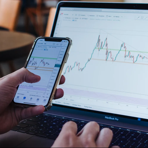 Man Trading On Mobile And Desktop